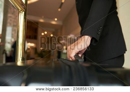 Close-up Image Of Porter Taking Suitcase To Hotel Room