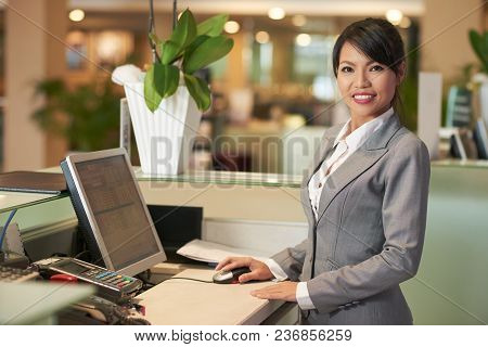 Portrait Of Cheerful Asain Receptionist Smiling And Looking At Camera