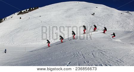 Young, Female Skier, Jumping In The Air On Skis, On A Sunny Day In Meribel, The French Alps.