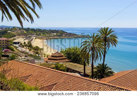 View Of Coastline Of Costa Dorada In Miami Platja, Sea, Beach, Palms And Tiled Roofs Of Houses With