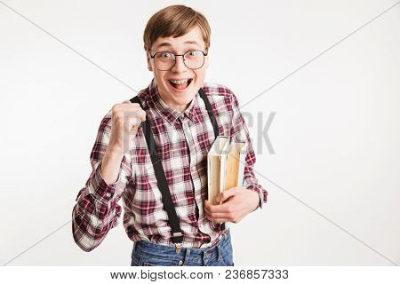 Portrait of an excited young school nerd guy holding book and celebrating isolated over white background