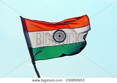 Flag Of India On The Mast. Indian Flag Develops Against The Background Of The Blue Cloudless Sky.