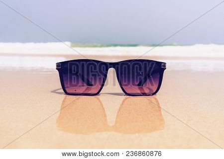 Close-up Of Seashells, Straw Hat, Glasses That Lie On The Sea Sand,