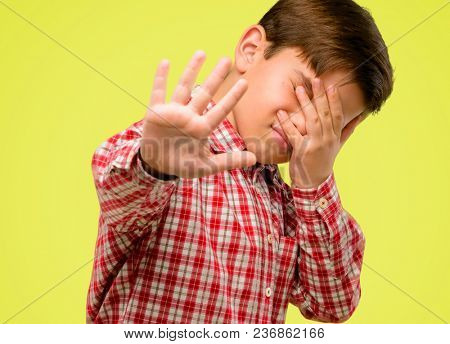 Handsome toddler child with green eyes stressful and shy keeping hand on head, tired and frustrated over yellow background
