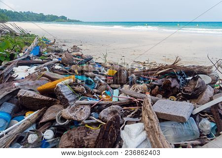 Pollution On The Beach Of Tropical Sea. Plastic Garbage, Foam, Wood And Dirty Waste On Beach In Summ