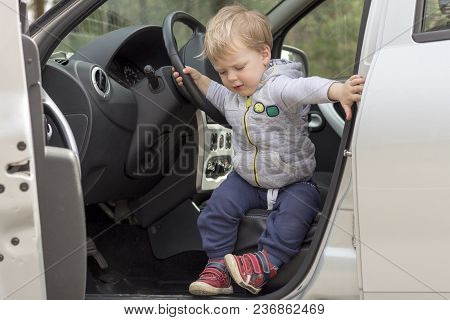 Little Boy Sitting In The Car And Going To Go Out.