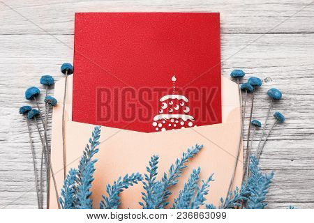Festive Postcard In An Envelope And Flowers On A Wooden Background