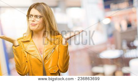 Beautiful young woman doubt expression, confuse and wonder concept, uncertain future shrugging shoulders at restaurant
