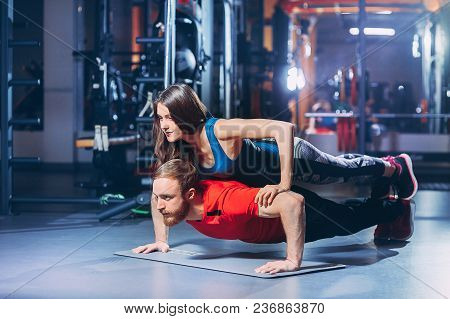 Young Sporty Couple Exercising Together In Gym. Man Doing Push Ups While Girl Lying On Him.