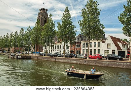 Weesp, Northern Netherlands - June 23, 2017. Boat Passing By Wooded Wide Canal With Brick Houses And