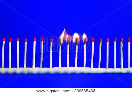 Line Of Red Unused And Four Burning Safety Matches On Bright Blue Background With Copy Space For Tex