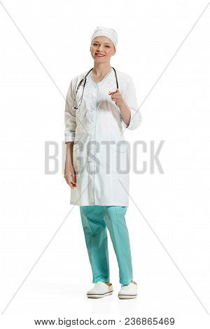 Beautiful Smiling Young Woman In White Coat Pointing At Camera. Full Length Shot Isolated On White B