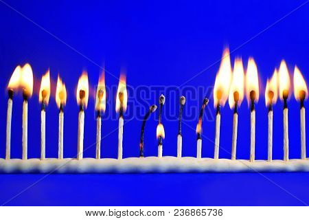 Line Of Seventeen Burning Safety Matches On Bright Blue Background With Copy Space For Text. Concept