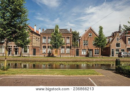 Tree-lined Canal With Streets On The Banks And Brick Houses On Sunny Day In Weesp. Quiet And Pleasan