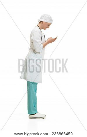 Beautiful Young Woman In White Coat Posing At Studio With Mobile Phone. Full Length Shot Isolated On