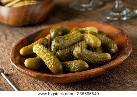 A Bowl Of Baby Dill Pickles On A Rustic Wood Table Top.