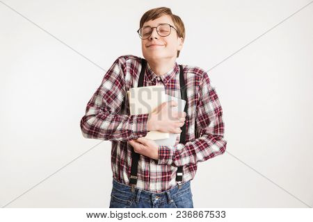 Portrait of an excited young school nerd guy holding book isolated over white background