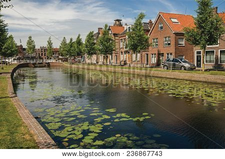 Weesp, Northern Netherlands - June 23, 2017. Canal With Street On The Banks, Brick Houses And Bascul