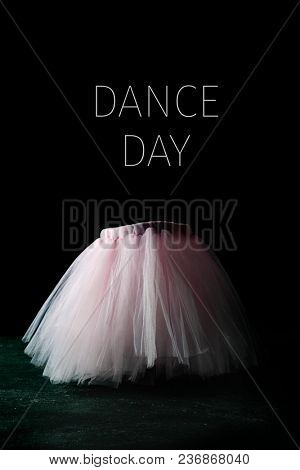 a pink tutu and the text dance day against a black background