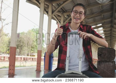 Asian Woman Wearing Casual Clothes Sitting With Suitcase Luggage Baggage Waiting For Train At Railwa