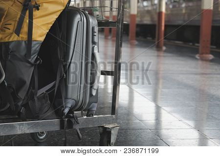 Yellow Backpack On Luggage Trolley At Train Station. Baggage Cart On Platform. Travel, Journey Conce
