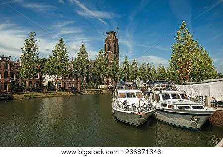 Boats Moored On The Canal Margin, Trees And Brick Buildings Under A Sunny Blue Sky At Weesp. Quiet A