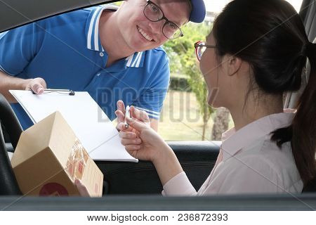 Woman On Car Signing Signature On Clipboard To Receive Package From Delivery Man. Male Postal Courie