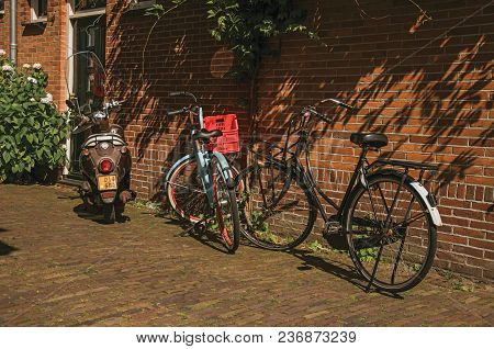 Bicycles And Scooter In Front Of Brick House In A Narrow Street Corner Under Sunny Blue Sky At Weesp