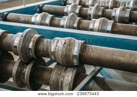 Metal Rolls Of Roll Forming Machine Close Up At Sandwich Panel Factory Or Metalwork Manufacturing, T
