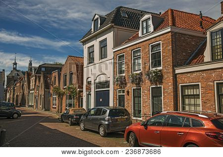 Weesp, Northern Netherlands - June 23, 2017. Brick Houses, Cars And Church At The End Of Street, Und