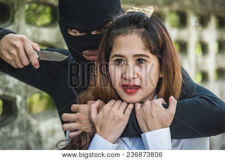 The Robber Man Holds A Knife, By Locking The Neck Of People Woman On Street
