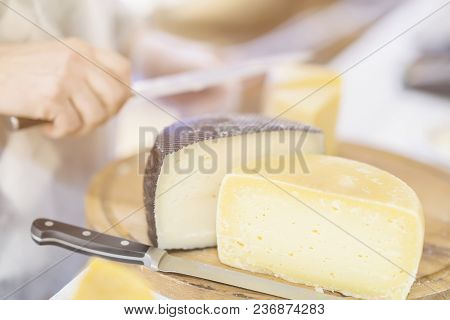 Cheese Heads On Market Counter, Seller Sells Cheese, Cut Cheese Heads On Wooden Market Board. Select