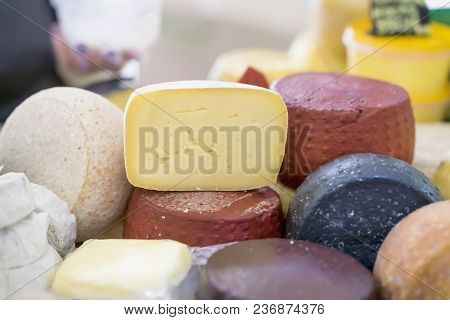 Cheese Wheels Different Grades And Cut Pieces On Market Counter, Colorful Colors. Gastronomic Dainty