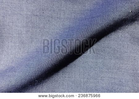 A Fold Across Thin Blue Jeans Fabric