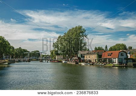 Vecht River With Bridge, Boats On The Banks And Brick Houses On A Sunny Day In Weesp. Quiet And Plea