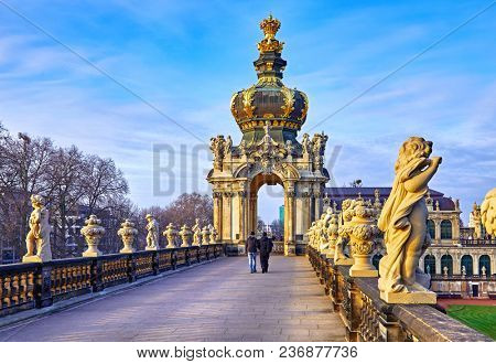 Dresden Germany Zwinger Palace statues, sculptures and architectural details in baroque and neo-Renaissance style at roofs of famous german landmark in old town. Evening sunset and blue sky.