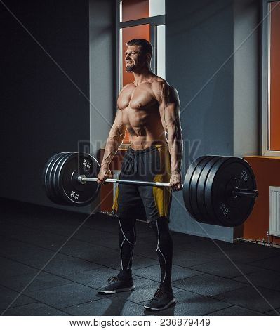 European Caucasian Athletic Man Doing Deadlift With Heavy Barbell. Man Lifting Barbell Opposite Wind