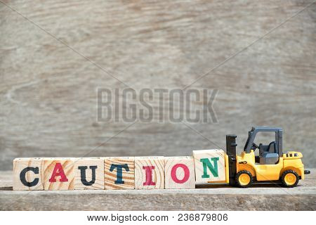 Toy Forklift Hold Letter Block N To Complete Word Caution On Wood Background