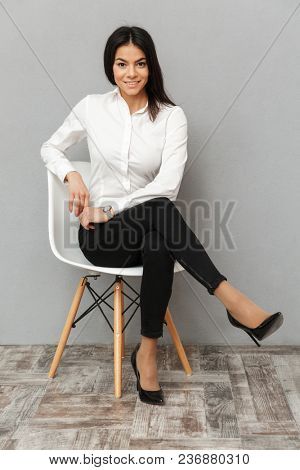 Full length image of happy business woman in formal wear sitting on chair in office isolated over gray background