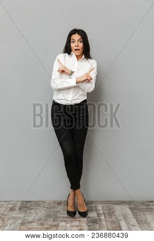 Full length image of stylish woman in formal wear smiling at camera and pointing fingers aside on copy space with crossed arms isolated over gray background