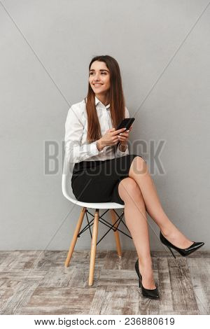 Full length portrait of cheerful office woman with long brown hair in business wear sitting on chair and looking aside while using smartphone isolated over gray background