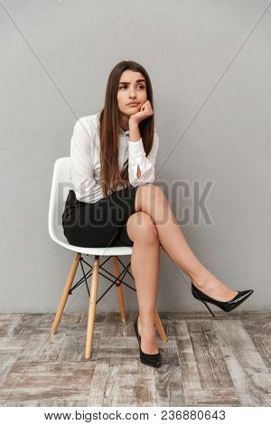 Full length portrait of caucasian woman with long brown hair in business wear sitting on chair with boring look and propping his head isolated over gray background