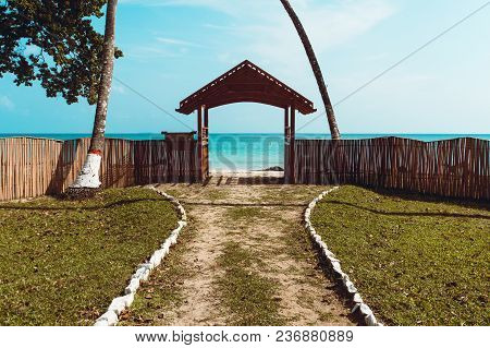 Access To Sea. Gate To The Sea - View From Road To The Gulf Of Mexico With Walls On Sides And Palm T