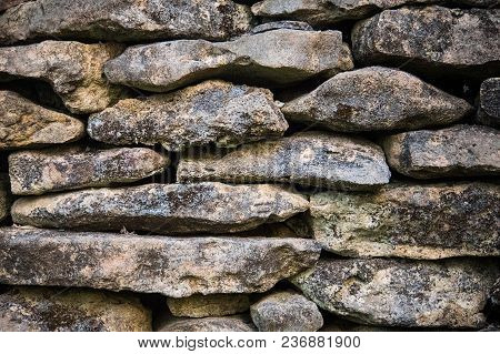 Background Of Old Stones In The Wall. The Texture Of The Stone Covered With Moss