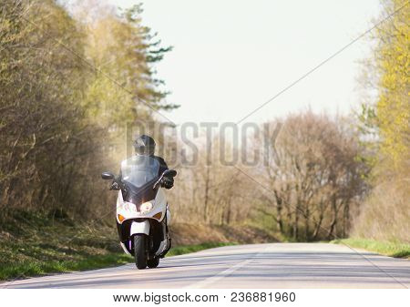 A Man Enjoys While Riding A Motorcycle Scooter On Roads Out Of Town And Crowds