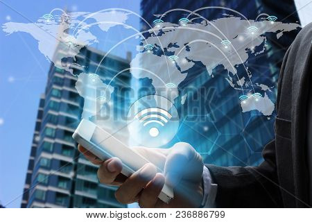 Businessman Hand Use Smartphone With Wifi Icons Connection And Network Communication On Map World.