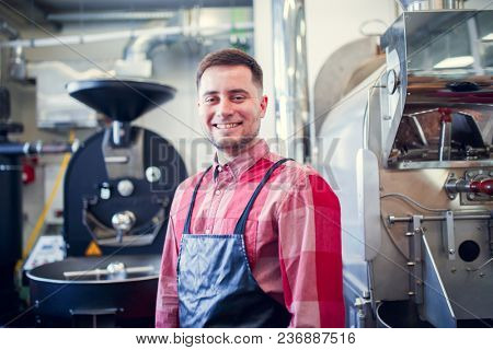 Picture of young man in apron on background of industrial coffee grinder