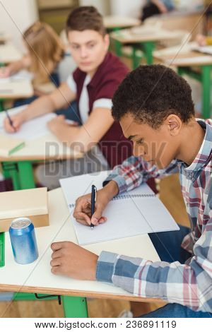 Elevated View Of African American Teenage Schoolboy Writing In Textbook And Classmates On Behind