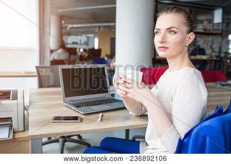 Beautiful Woman Is Sitting In Chair And Holding A Cup Of Tea. She Took A Pause After Some Hard-worki