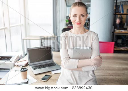 Portrait Of Happy, Good-looking And Confident Woman Sitting T The Adge Of The Table And Looking To T